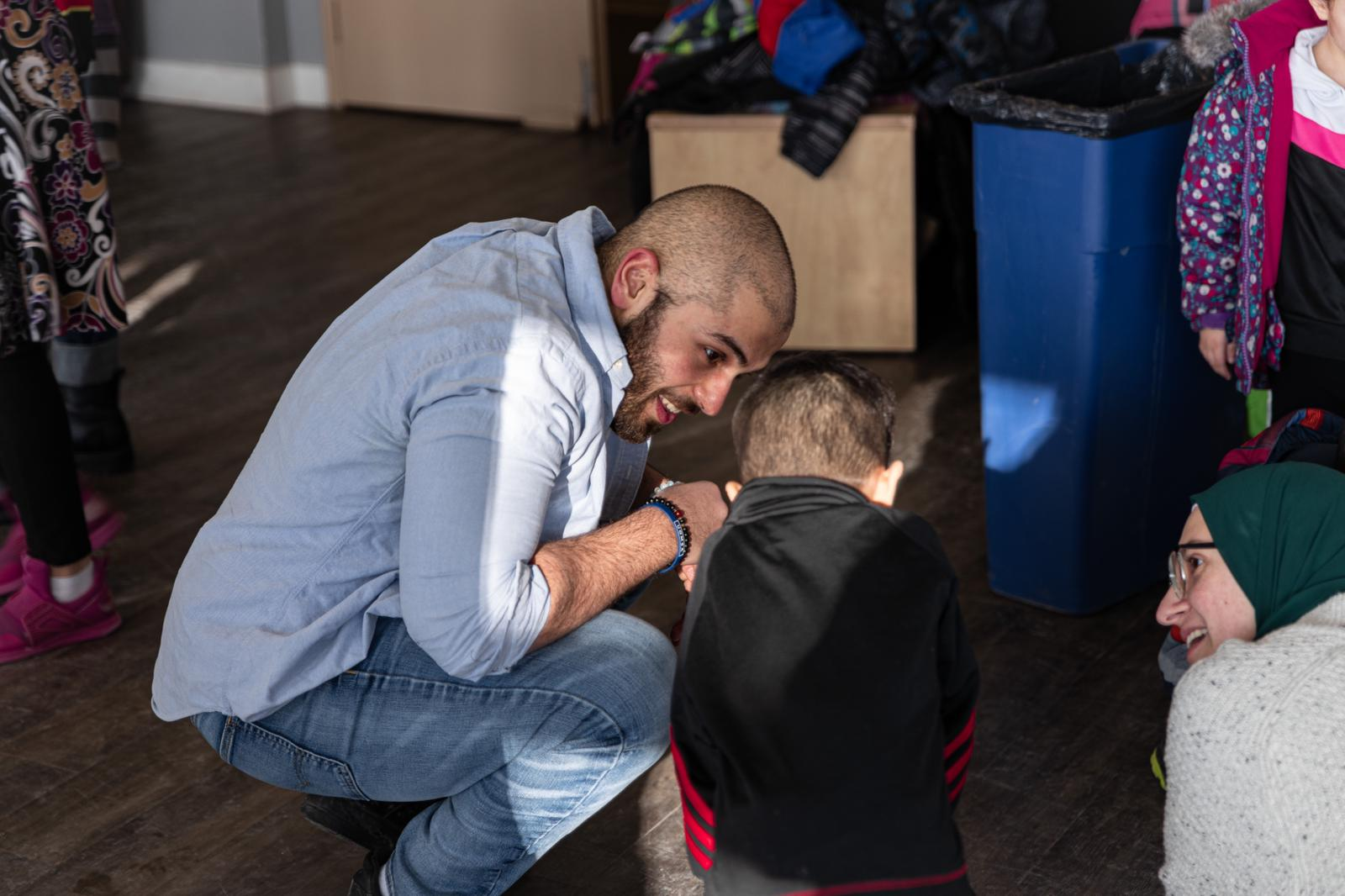 A mentor crouches down to talk to a child